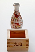 Square wooden sake bowl in front of carafe