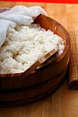 Boiled sushi rice in wooden bowl with cloth