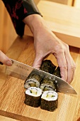 Cutting rolled sushi into pieces