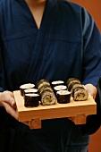 Person in blue kimono serving maki-sushi