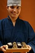 Woman in blue kimono serving maki-sushi