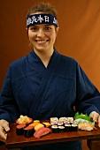 Woman serving sushi platter