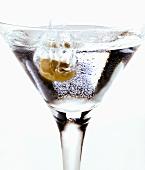 Olive falling into Martini glass