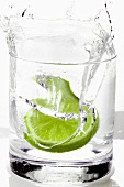Slice of lime falling into a drink