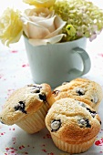 Blueberry muffins in front of bouquet of flowers