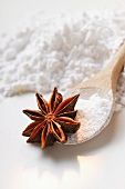 Star anise and icing sugar on kitchen spoon