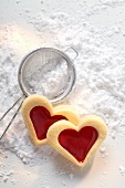 Sweet pastry hearts with raspberry jam on icing sugar