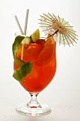 Cocktail with fruit, lime zest and cocktail umbrella