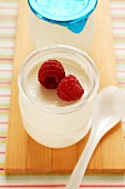 Jar of yoghurt with fresh raspberries