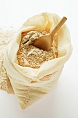 Wholemeal flour in sack with wooden scoop