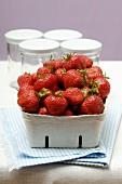 Fresh strawberries in cardboard punnet; jam jars