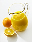 Orange juice in glass jug; fresh oranges