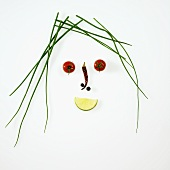 Face made from chives, vegetables and lime