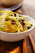 Raw vegetable salad with leeks, raisins and oranges