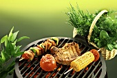 Chop, kebab, sweetcorn and tomato on barbecue; fresh herbs