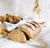 Sunflower seed bread, a slice cut; bread rolls in bread basket