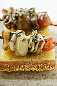 Barbecued pork kebabs on sesame baguette