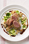 Venison fillet in bacon, forest mushrooms & Brussels sprouts
