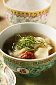 Broth with won tons, chili sauce & strips of lemon leaves