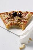 Angebissenes Stück Pizza mit Thunfisch und Oliven