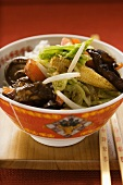 Vegetables and mushrooms cooked in wok on rice (China)