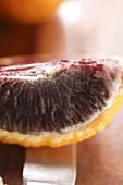 Wedge of blood orange on knife