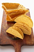 Assorted taco shells on chopping board
