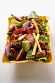 Salad with mince, vegetables, cheese in taco shell (Mexico)