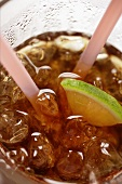 Cola with ice cubes and lemon (close-up)