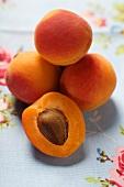 Aprikosen, eine halbiert, auf geblümtem Tischtuch