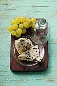 Roquefort with cheese dome and green grapes on chopping board