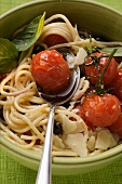 Spaghetti with cherry tomatoes, olives and Parmesan shavings