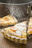 Sprinkling apricot tart with icing sugar