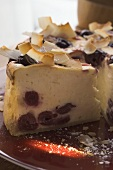 Cheesecake with cherries and coconut shavings, a piece cut