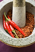 Chili peppers and chili powder in mortar (close-up)
