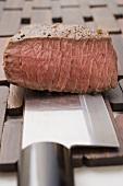 Beef steak, a piece cut off, on Asian knife