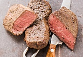 Two beef steaks, with knife and meat fork