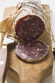 Italian salami, a slice cut, on chopping board