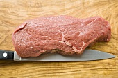 Beef sirloin with knife on chopping board