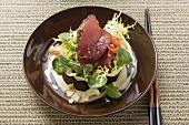 Raw tuna fillets with poppy seeds on salad in bowl