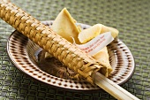 Fortune cookies and chopsticks in woven wrapper on plate