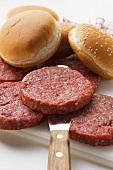 Raw burgers and hamburger rolls