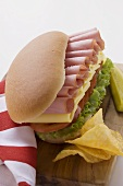 Sub sandwich with crisps and gherkin on chopping board