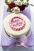 Birthday cake on pale purple box, roses
