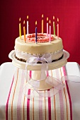 Birthday cake with burning candles on cake stand