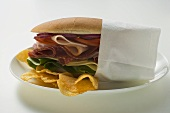Salami, ham, cheese and salad sandwich in napkin with crisps
