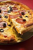 Pizza with salami, cheese and olives, a piece cut