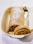 Fruit strudel with nuts and icing sugar, partly sliced