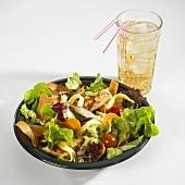 Green salad with chicken breast & vegetables, glass of lemonade