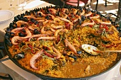 Paella in large frying pan on table in restaurant